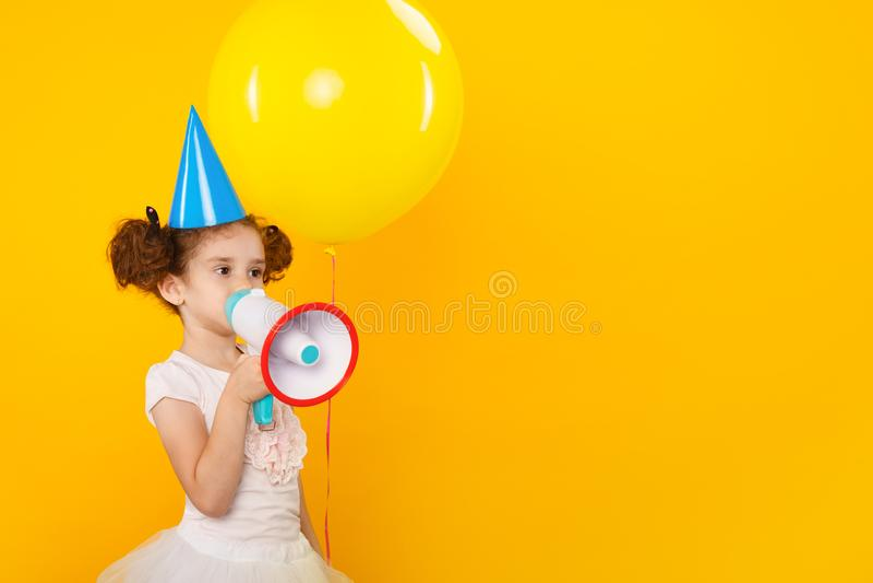 Petite fille caucasienne annoncer par le mégaphone d'isolement sur le fond jaune avec l'espace de copie t?l?phone noir de r?cepte image libre de droits