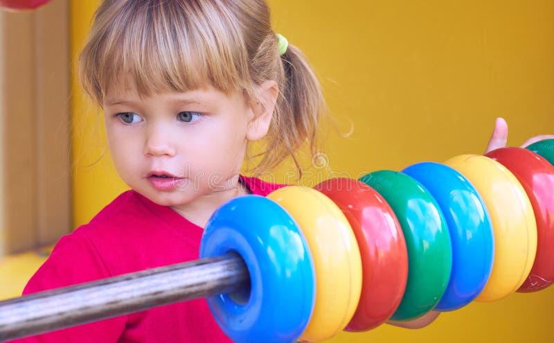 Petite fille caucasienne dans le T-shirt rouge jouant avec l'abaque sur le terrain de jeu dehors dans le jour d'été photos stock