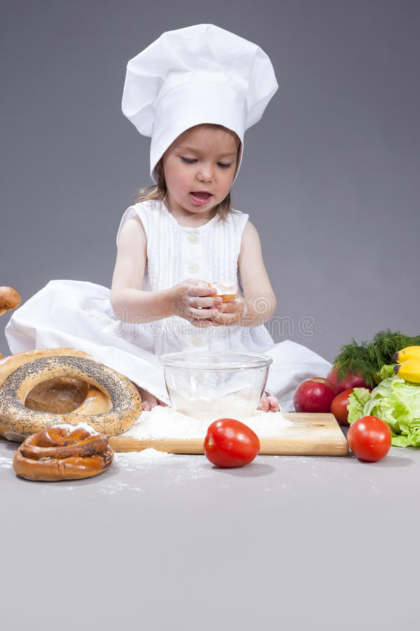 Petite fille caucasienne de sourire drôle dans le cuisinier Uniform Making un mélange de farine, des oeufs et des légumes dans le photos libres de droits
