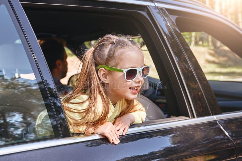 Petite fille caucasienne gaie mignonne s'asseyant à l'intérieur de la voiture, regardant la fenêtre et le sourire Voyage par la r images stock