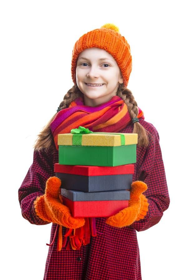 Petite fille caucasienne heureuse de sourire dans la calotte, l'?charpe et des mitaines oranges avec la pile de Giftboxes color? images stock