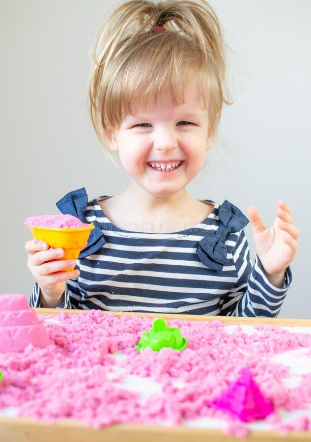 Petite fille caucasienne heureuse jouant avec le sable cinétique rose à la maison images stock