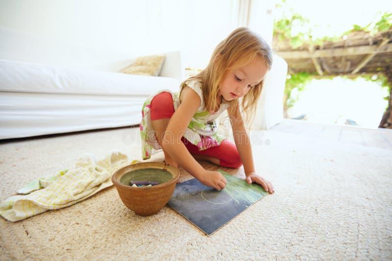 Petite fille caucasienne mignonne dessinant à la maison photo stock