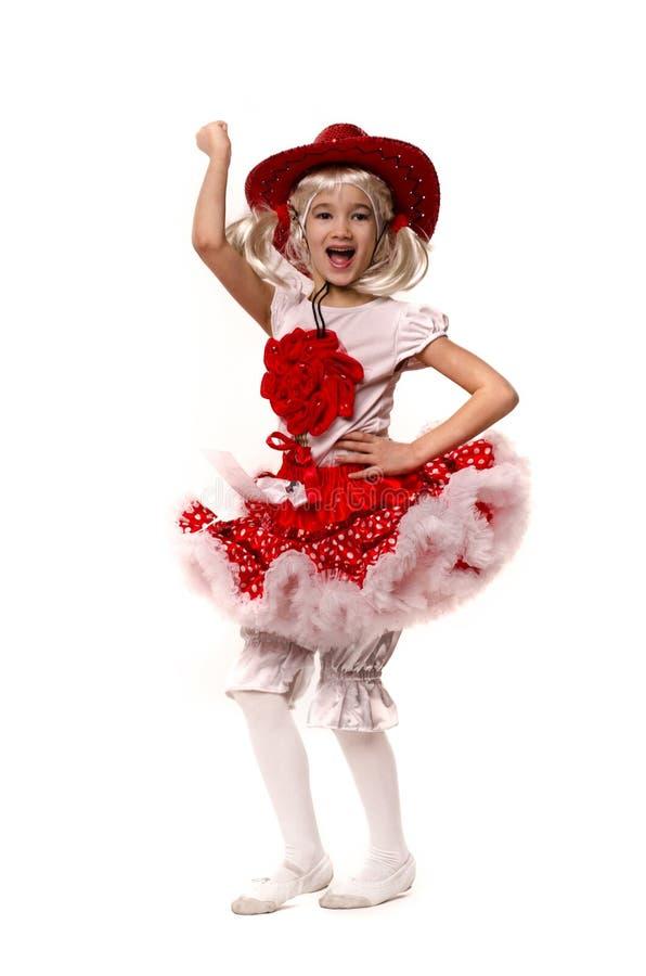 Petite fille caucasienne mignonne utilisant la jupe rouge, le T-shirt avec des fleurs et le chapeau de cowboy d'isolement sur le  image libre de droits
