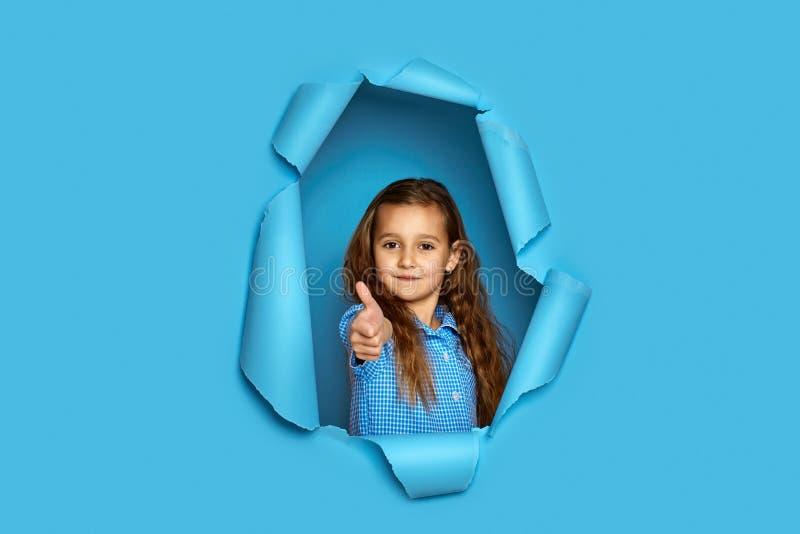 Petite fille caucasienne montrant des pouces photos stock