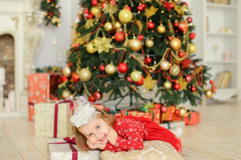 Petite fille caucasienne portant la robe rouge se trouvant près de l'arbre et des présents de Noël photos stock