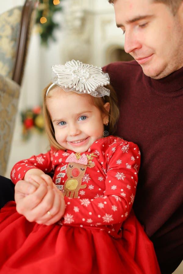 Petite fille caucasienne s'asseyant avec le père et la robe rouge de port image stock