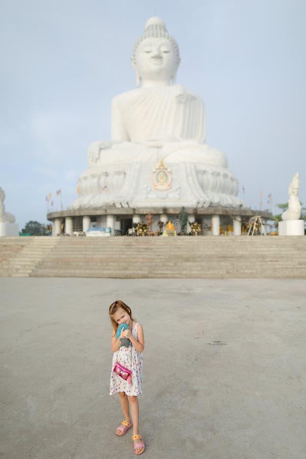 Petite fille caucasienne se tenant près de la statue blanche de Bouddha à Phuket image libre de droits
