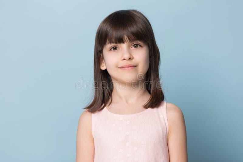 Petite fille châtain aux yeux bruns adorable d'isolement sur le bleu photos libres de droits