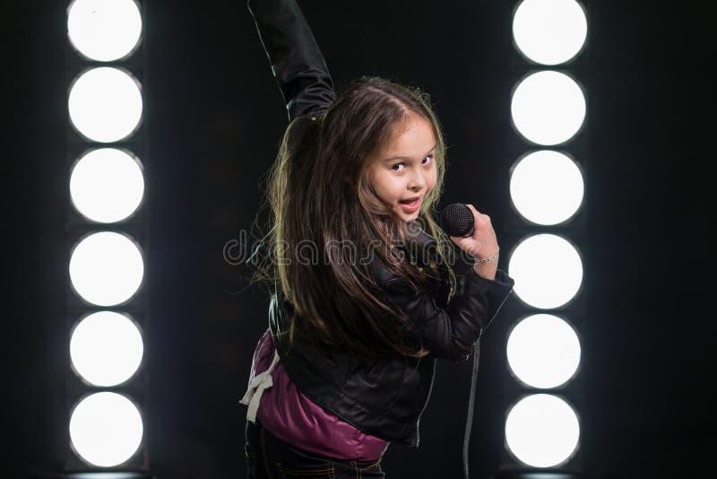 Petite fille chantant devant des lumières d'étape photographie stock