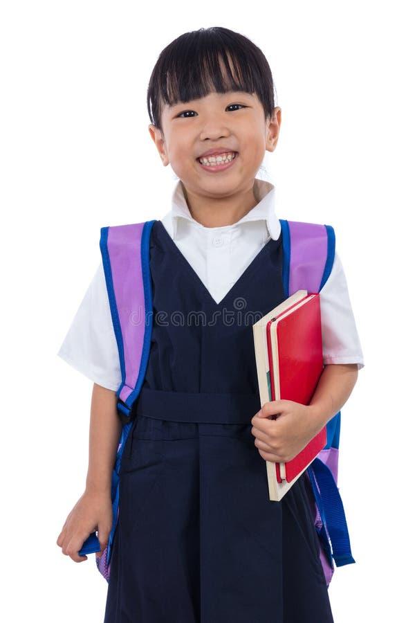 Petite fille chinoise asiatique d'école primaire tenant des livres avec le sac image libre de droits