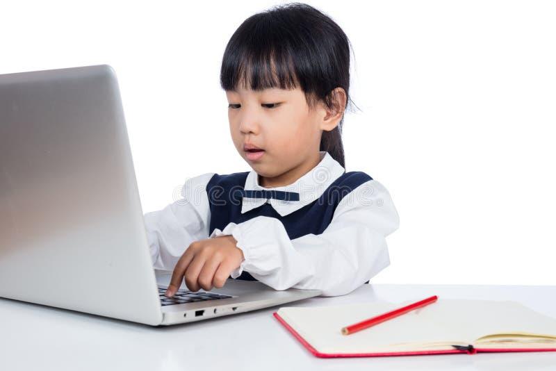 Petite fille chinoise asiatique dans l'uniforme étudiant avec l'ordinateur portable photos libres de droits