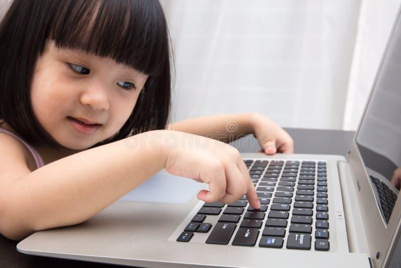 Petite fille chinoise asiatique de sourire à l'aide de l'ordinateur portable à la maison image libre de droits