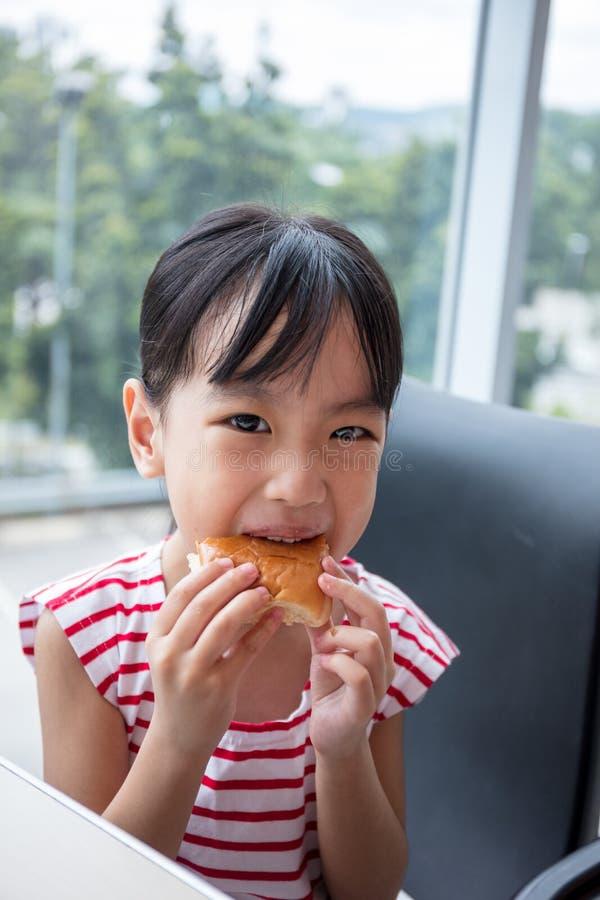 Petite fille chinoise asiatique mangeant du pain photos stock