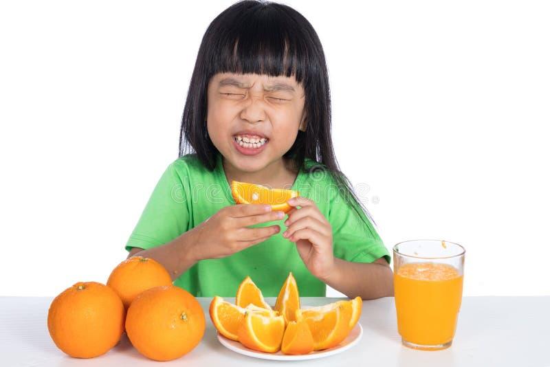 Petite fille chinoise asiatique mangeant l'orange amère et faisant la grimace images libres de droits