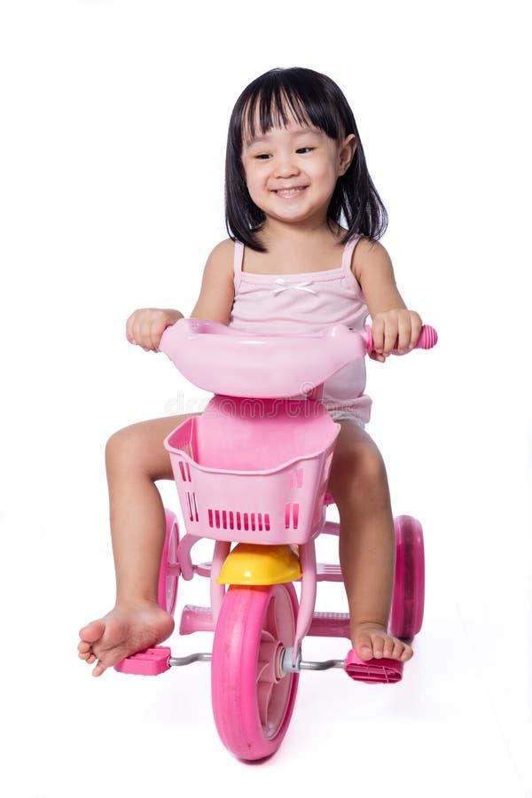 Petite fille chinoise asiatique montant un tricycle de jouet photo libre de droits