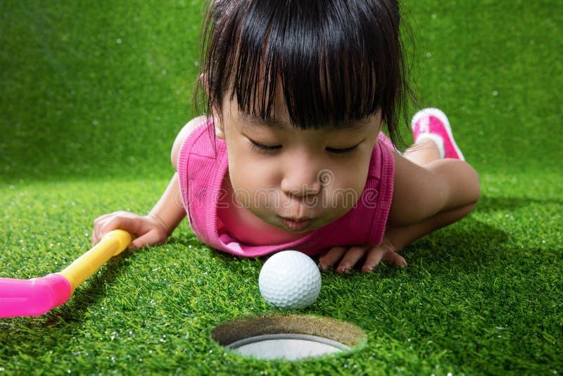 Petite fille chinoise asiatique soufflant la boule dans un trou photo stock