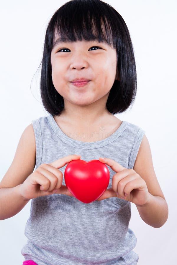 Petite fille chinoise asiatique tenant le coeur rouge photos libres de droits