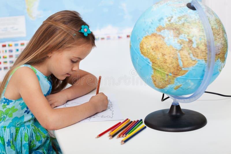 Petite fille colorant la carte du monde dans la classe de géographie photos libres de droits