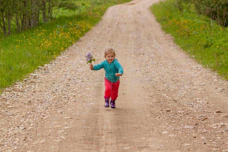 Petite fille courant en bas de la route photographie stock