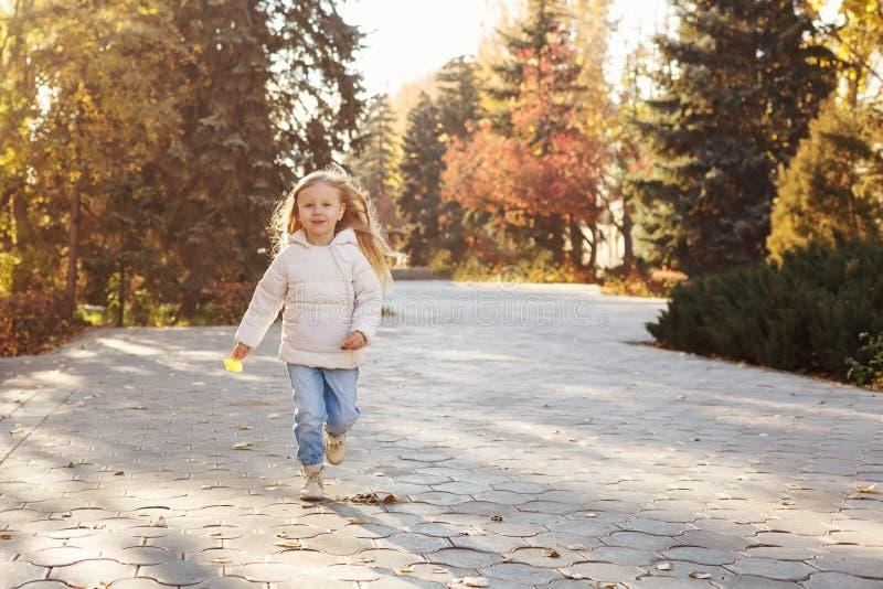 Petite fille courant en parc d'automne image libre de droits