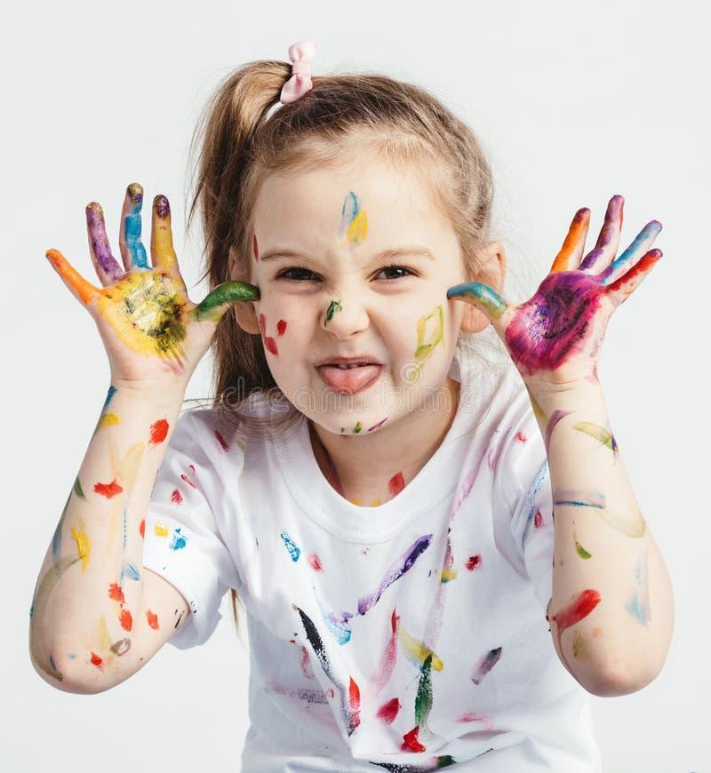 Petite fille couverte en peinture faisant les visages drôles images stock