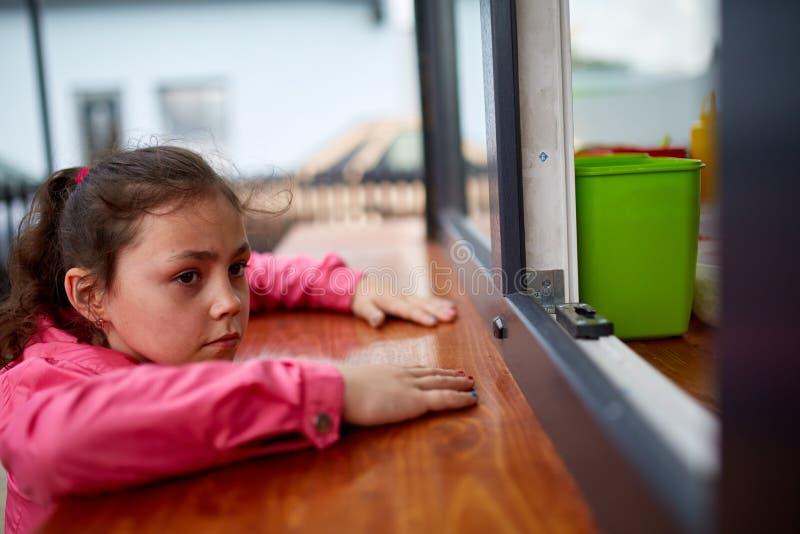 Petite fille curieuse attendant son hamburger dans la fenêtre de boutique de rue image stock