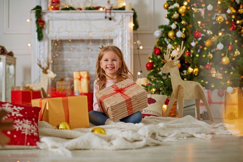 Petite fille curieuse enthousiaste souriant, cadeaux s'ouvrants de Noël Arbre et maison de Noël admirablement décorés avec des lu images stock