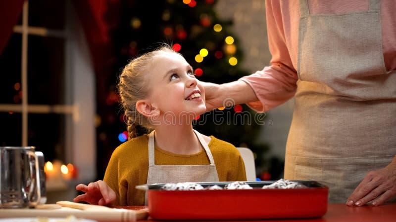 Petite fille délicate goûtant secrètement le petit pain de chocolat, préparation de Noël photos libres de droits