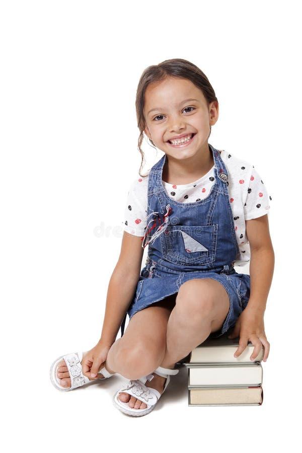 Petite fille d'étudiant s'asseyant sur la pile de livres image stock
