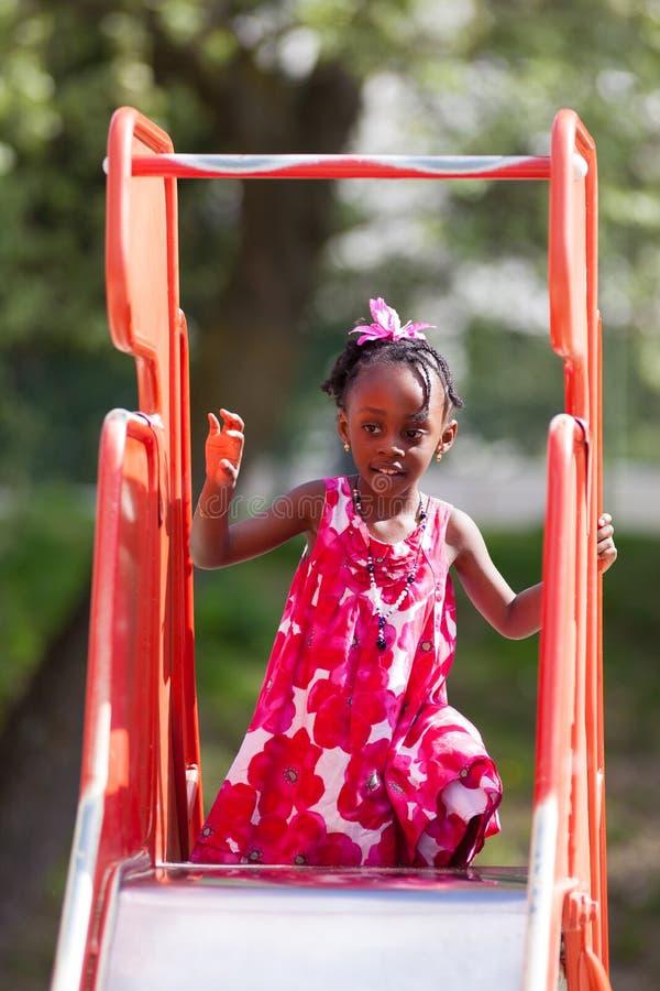 Petite fille d'afro-américain mignon à la cour de jeu image stock