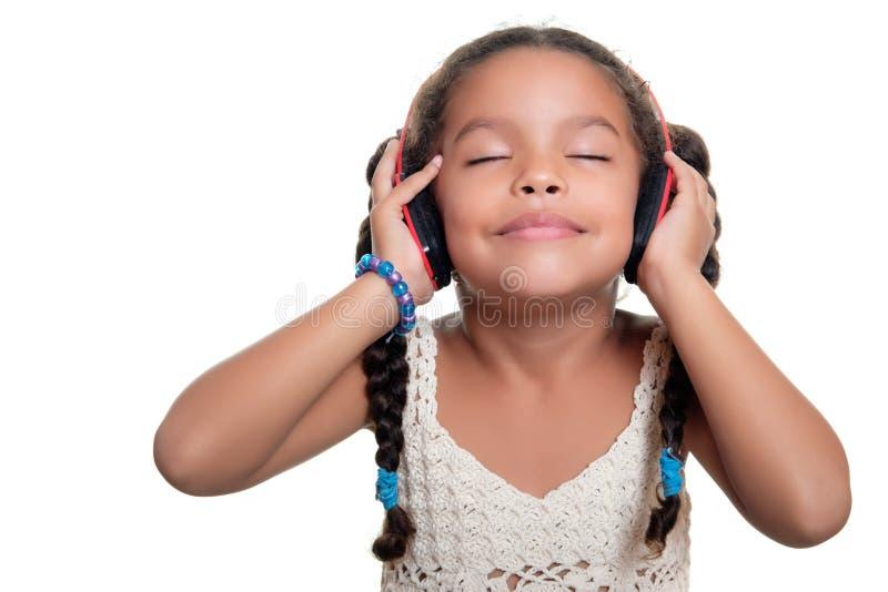 Petite fille d'afro-américain mignon écoutant la musique sur la radio photos stock