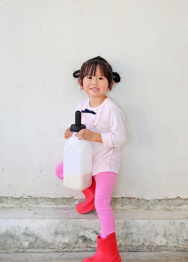 Petite fille d'agriculteur tenant la bouteille à lait dans la ferme photo stock