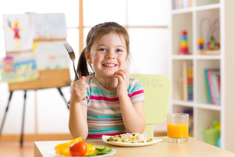 Petite fille d'enfant avec la nourriture saine tout préparée de fourchette photo libre de droits