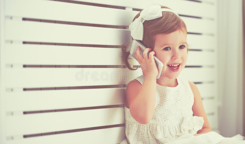 Petite fille d'enfant avec le smartphone de téléphone image stock