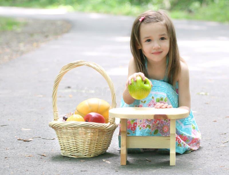 Petite fille d'enfant en bas âge en stationnement jouant avec le fruit images libres de droits