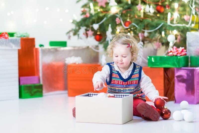 Petite fille d'enfant en bas âge ouvrant son cadeau de Noël sous un bel arbre de Noël photographie stock libre de droits