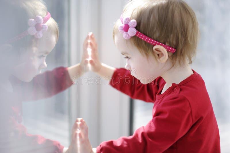 Petite fille d'enfant en bas âge regardant par un hublot images libres de droits