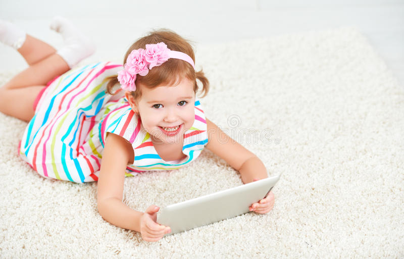 Petite fille d'enfant heureux jouant dans la tablette images stock