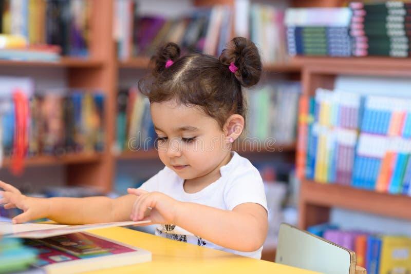 Petite fille d'enfant heureux lisant un livre photos libres de droits