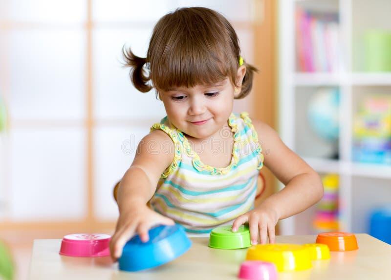 Petite fille d'enfant jouant avec des jouets à l'intérieur images libres de droits