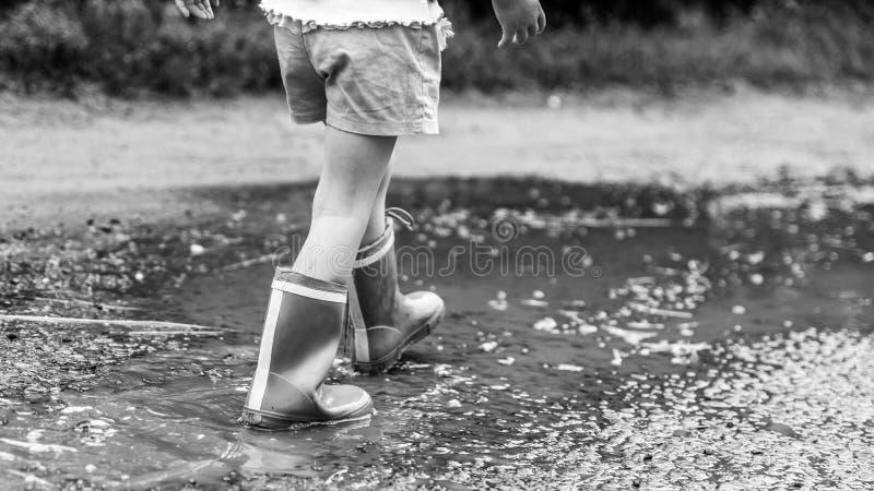 Petite fille dans des bottes en caoutchouc marchant le long de l'eau après pluie, route ruinée, campagne, effet monochrome photographie stock libre de droits