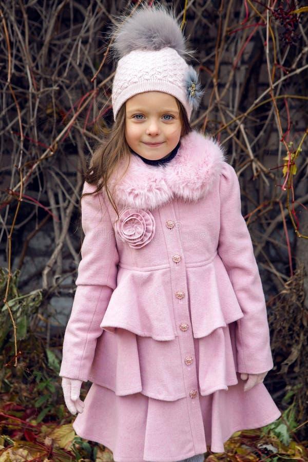 Petite fille dans des lames d'automne photo stock