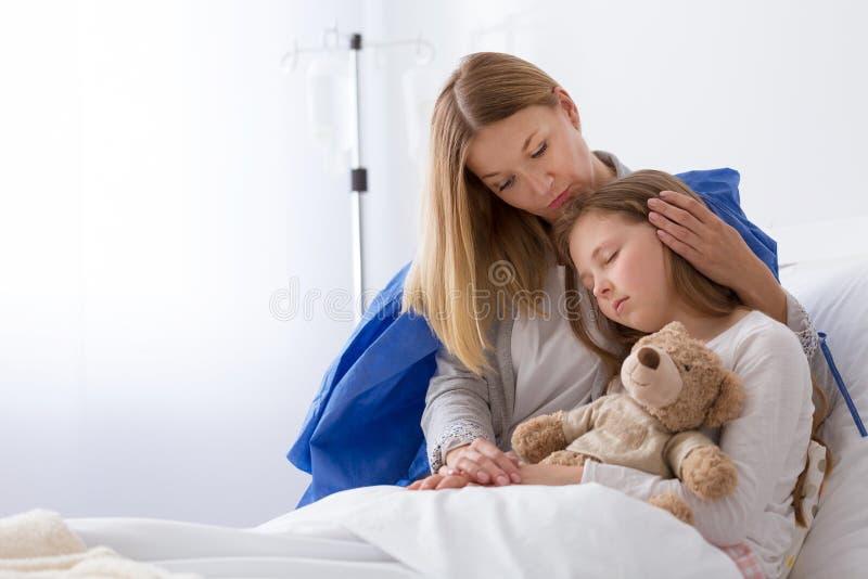 Petite fille dans l'hôpital et sa mère supperting la photos stock