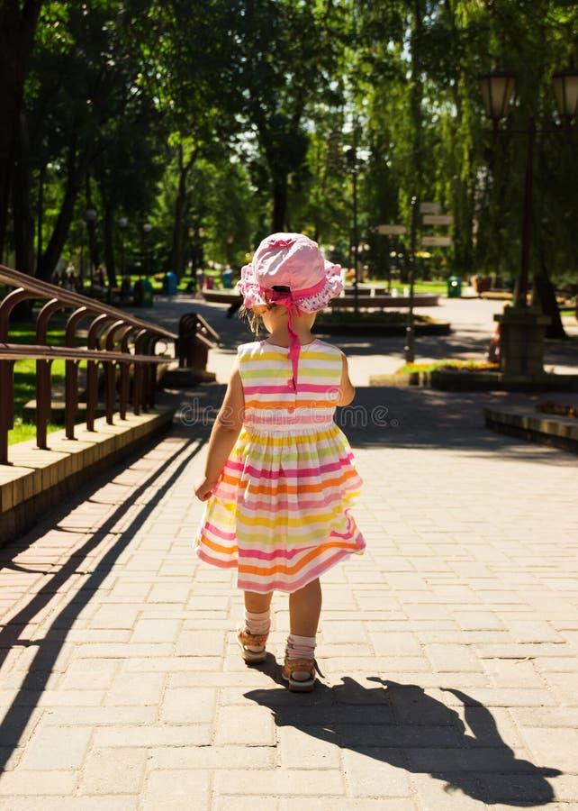 Petite fille dans la belle robe fonctionnant loin sur la route en parc photos libres de droits
