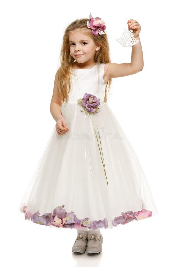 Petite fille dans la belle robe retenant des cloches photographie stock