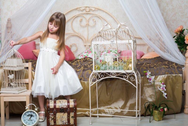 Petite fille dans la chambre à coucher tenant une cage image stock
