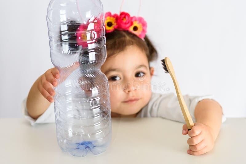 Petite fille dans la chemise blanche tenant la brosse à dents en bambou et la bouteille en plastique image stock