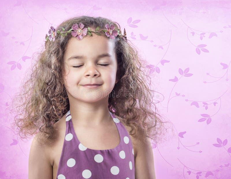 Petite fille dans la couronne de fleur avec des yeux fermés sur le fond rose image stock