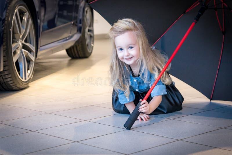 Petite fille dans la pièce d'exposition de voiture photographie stock